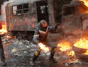 A protester throws a Molotov cocktail during clashes with police in central Kiev, Ukraine, Wednesday, Jan. 22, 2014. Three people have died in clashes between protesters and police in the Ukrainian capital Wednesday, according to medics on the site, in a development that will likely escalate Ukraine's two month-long political crisis. The mass protests in the capital of Kiev erupted after Ukrainian President Viktor Yanukovych spurned a pact with the European Union in favor of close ties with Russia, which offered him a $15 billion bailout. (AP Photo/Efrem Lukatsky)