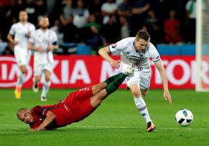 Portugal's Pepe, left, hits Iceland's Jon Dadi Bodvarsson with his boots during the Euro 2016 Group F soccer match between Portugal and Iceland at the Geoffroy Guichard stadium in Saint-Etienne, France, Tuesday, June 14, 2016. (AP Photo/Pavel Golovkin)