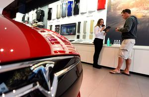 A salesrep (L) helps a customer pre-order the as yet unseen Tesla Model 3, in the Tesla store on the Third Street Promenade in Santa Monica, California, on March 31, 2016.   / AFP PHOTO / ROBYN BECKROBYN BECK/AFP/Getty Images