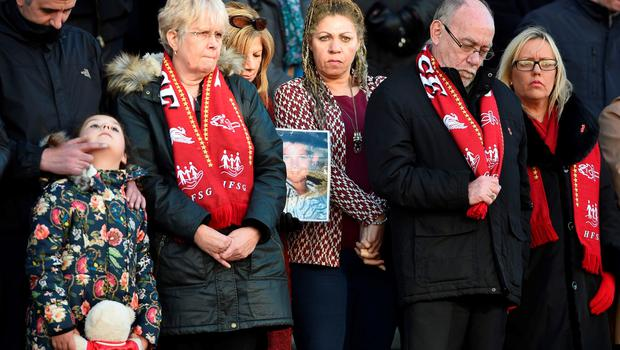 Relatives of the victims of the 1989 Hillsborough disaster hold photographs as they gather on the steps of St George's Hall in Liverpool, north west England on April 27, 2016, in remembrance of the Liverpool fans who died in the Hillsborough football stadium disaster. Thousands of sympathisers paid an emotional tribute to the Hillsborough disaster victims today after a landmark inquest found that 96 Liverpool football fans were unlawfully killed. / AFP PHOTO / PAUL ELLISPAUL ELLIS/AFP/Getty Images