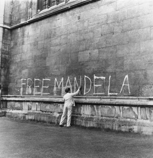 (FILE PHOTO) Former South African President Nelson Mandela Has Died Aged 95 A man washing a 'Free Mandela' slogan off the side of King's College Chapel, Cambridge.   (Photo by Peter Dunne/Getty Images)