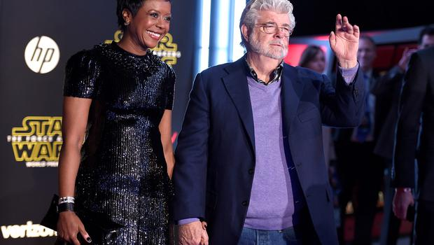 """Mellody Hobson, left, and George Lucas arrive at the world premiere of """"Star Wars: The Force Awakens"""" at the TCL Chinese Theatre on Monday, Dec. 14, 2015, in Los Angeles. (Photo by Jordan Strauss/Invision/AP)"""