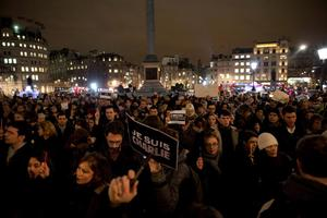 People hold up pens and posters reading 'I am Charlie' in French as they take part in a vigil of people, including many who were French, to show solidarity with those killed in an attack at the Paris offices of weekly newspaper Charlie Hebdo, in Trafalgar Square, London, Wednesday, Jan. 7, 2015. Masked gunmen stormed the Paris offices of a weekly newspaper that caricatured the Prophet Muhammad, methodically killing 12 people Wednesday, including the editor, before escaping in a car. It was France's deadliest postwar terrorist attack. (AP Photo/Matt Dunham)