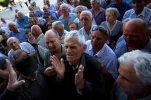Elderly people argue with a bank worker as they wait to be allowed into the bank to withdraw a maximum of 120 euros ($134) for the week in Athens, Monday, July 6, 2015. Greeces Finance Minister Yanis Varoufakis has resigned following Sundays referendum in which the majority of voters said no to more austerity measures in exchange for another financial bailout. (AP Photo/Emilio Morenatti)