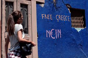 "A woman walks past a slogan written on a wall in Athens on July 7, 2015.  Eurozone leaders will hold an emergency summit in Brussels on July 7 to discuss the fallout from Greek voters' defiant ""No"" to further austerity measures, with the country's Prime Minister Alexis Tsipras set to unveil new proposals for talks. AFP PHOTO / LOUISA GOULIAMAKILOUISA GOULIAMAKI/AFP/Getty Images"
