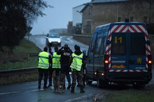 Police officers stop a car at a check point on January 9, 2015 outside Longpont, France. A huge manhunt for the two suspected gunmen in Wednesday's deadly attack on Charlie Hebdo magazine has entered its third day.  (Photo by Pascal Le Segretain/Getty Images)