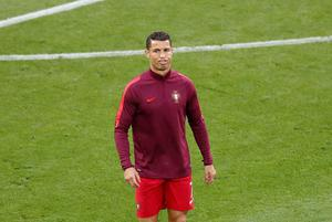 Portugal's Cristiano Ronaldo grimaces while warming up before the Euro 2016 Group F soccer match between Portugal and Iceland at the Geoffroy Guichard stadium in Saint-Etienne, France, Tuesday, June 14, 2016. (AP Photo/Michael Sohn)