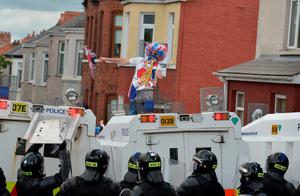 BELFAST, NORTHERN IRELAND - JULY 13:  A Loyalist breaks through a police barrier and taunts police officers as Orangemen are prevented from progressing on the return journey towards the controversial Ardoyne flashpoint the Twelfth of July parade on July 13, 2015 in Belfast, Northern Ireland.