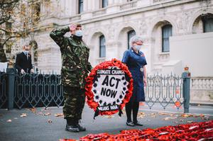 British Army veteran and XR member Donald Bell observed two minutes' silence before hanging a wreath of poppies on the Cenotaph. (TheLightscaper/PA)