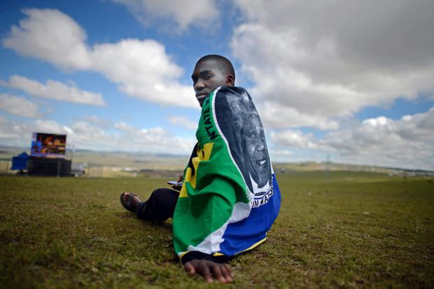QUNU, SOUTH AFRICA - DECEMBER 15:  People watch the big screens at the site where former South African President Nelson Mandela will be buried on his family's property in his childhood village on December 15, 2013 in Qunu, South Africa. Mr. Mandela passed away on the evening of December 5, 2013 at his home in Houghton at the age of 95. Mandela became South Africa's first black president in 1994 after spending 27 years in jail for his activism against apartheid in a racially-divided South Africa.   (Photo by Jeff J Mitchell/Getty Images)