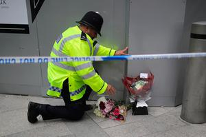 LONDON, ENGLAND - JUNE 04:  A police officer looks at floral tributes near the scene of last night's terrorist attack on June 4, 2017 in London, England. Police continue to cordon off an area after responding to terrorist attacks on London Bridge and Borough Market where 7 people were killed and at least 48 injured last night. Three attackers were shot dead by armed police.  (Photo by Christopher Furlong/Getty Images)