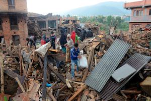 "People carry their belongings amidst the rubble of collapsed houses in Bhaktapur, on the outskirts of Kathmandu, on April 27, 2015, two days after a 7.8 magnitude earthquake hit Nepal. Nepalis started fleeing their devastated capital on April 27 after an earthquake killed more than 3,800 people and toppled entire streets, as the United Nations prepared a ""massive"" aid operation.  AFP PHOTO / PRAKASH MATHEMAPRAKASH MATHEMA/AFP/Getty Images"