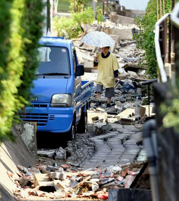 A resident walks through the debris after a magnitude-6.5 earthquake in Mashiki, Kumamoto prefecture, southern Japan, Friday, April 15, 2016.  More than 100 aftershocks from Thursday night's earthquake continued to rattle the region as businesses and residents got a fuller look at the widespread damage from the unusually strong quake, which also injured about 800 people. (Kyodo News via AP) JAPAN OUT, MANDATORY CREDIT