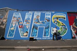 Artist Marty Lyons putting the finishing touches to a mural paying tribute to the NHS and key workers on the Falls Road in west Belfast, Northern Ireland. Photo by Kelvin Boyes  / Press Eye.
