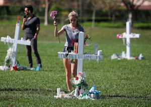PARKLAND, FL - FEBRUARY 16:  A young women places flowers at a memorial site that honors victims of the mass shooting at Marjory Stoneman Douglas High School, at Pine Trail Park on February 16, 2018 in Parkland, Florida. Police arrested 19-year-old former student Nikolas Cruz for killing 17 people at the high school.  (Photo by Mark Wilson/Getty Images)