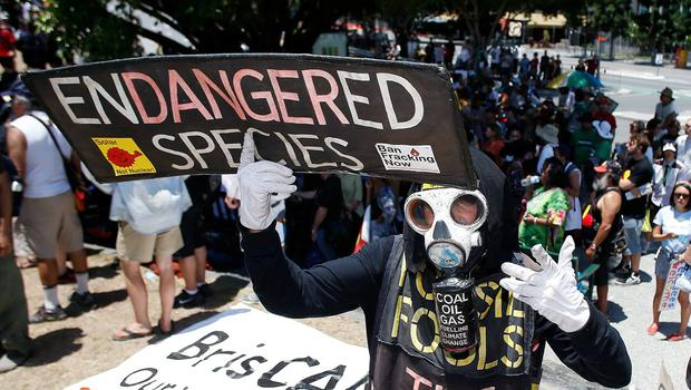 A man holds a placard during a protests against G20 leaders on November 15, 2014 in Brisbane, Australia. (Photo by Daniel Munoz/Getty Images)