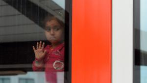A refugee girl waits in a regional train after arriving at the main train station in Munich, southern Germany, on September 05, 2015. Hundreds of refugees arrived in Germany on September 5, 2015 coming from Hungary and Austria. AFP PHOTO / CHRISTOF STACHECHRISTOF STACHE/AFP/Getty Images