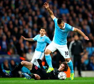 MANCHESTER, ENGLAND - APRIL 12:  Sergio Aguero of Manchester City is challenged by Adrien Rabiot of Paris Saint-Germain during the UEFA Champions League quarter final second leg match between Manchester City FC and Paris Saint-Germain at the Etihad Stadium on April 12, 2016 in Manchester, United Kingdom.  (Photo by Clive Brunskill/Getty Images)