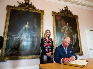 The Prince of Wales signing the visitors book at Palace Demense in Co. Armagh with Armagh Lord Mayor Mealla Campbell, sitting infront of portraits of his ancestors King George III, and Queen Charlotte, painted by Scottish portrait-painter Alan Ramsey. PRESS ASSOCIATION Photo. Picture date: Wednesday May 22, 2019. See PA story ROYAL Tour. Photo credit should read: Liam McBurney/PA Wire