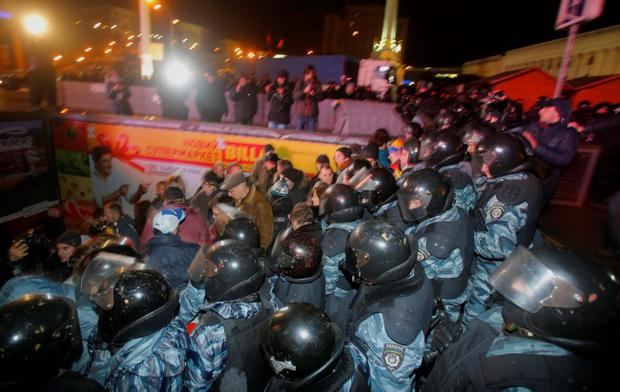 Ukrainian riot police push people to an underground crossing after dispersing a rally at the Independence Square in downtown Kiev, Ukraine, on Saturday, Nov. 30, 2013. Police in the Ukrainian capital broke up a large anti-government demonstration in the city center before dawn Saturday, swinging truncheons and injuring many. The riot police used tear gas when they dispersed the crowd of about 400 protesters who were demanding the resignation of President Viktor Yanukovych, demonstrators said. (AP Photo/Sergei Grits)