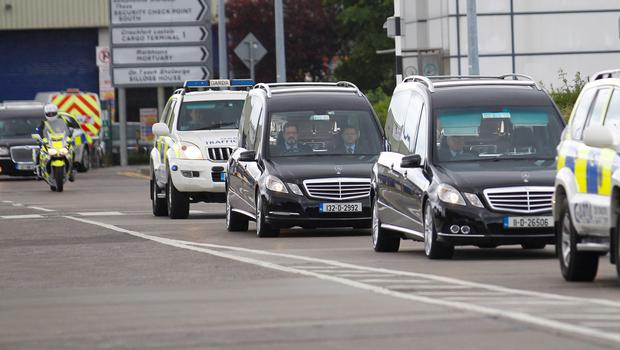 The bodies of four of the Irish students who died after a balcony collapsed in Berkeley, California arrive back at Dublin Airport. (AP Photo/Peter Morrison)