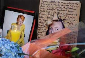 Memorabilia and bouquets of flowers are left in honor of David Bowie outside his New York apartment, Monday, Jan. 11, 2016. Bowie, the other-worldly musician who broke pop and rock boundaries with his creative musicianship, nonconformity, striking visuals and a genre-spanning persona he christened Ziggy Stardust, died of cancer Sunday. He was 69. (AP Photo/Mark Lennihan)