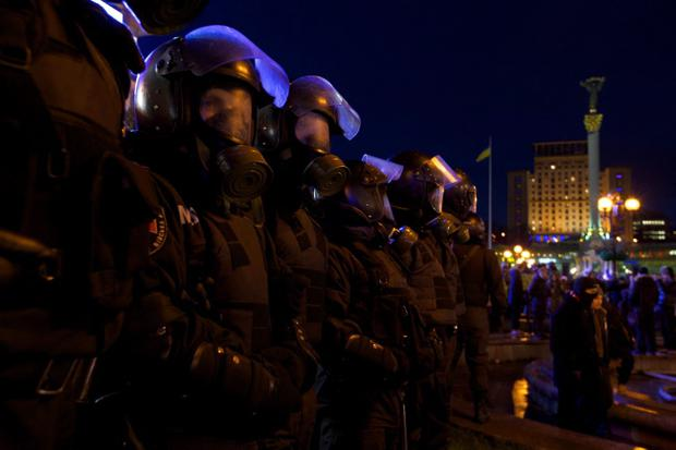 Ukrainian police officers wear gas masks as they surround the Independence square during an opposition rally in downtown Kiev, Ukraine, on Friday, Nov. 29, 2013. Thousands of demonstrators are gathering in Ukraine's capital after a deal that could have brought closer ties to the EU was shelved. Protesters are calling for the resignation of President Viktor Yanukovych, who ditched the free trade pact with the EU at Friday's summit in favor of closer ties with Russia. (AP Photo/Ivan Sekretarev)