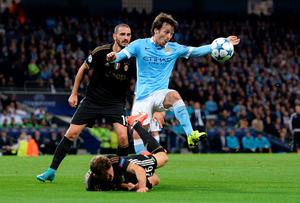 Manchester City's Spanish midfielder David Silva (R) fouls Juventus' defender from Switzerland Stephan Lichtsteiner (down) during a UEFA Champions League group stage football match between Manchester City and Juventus at the Etihad stadium in Manchester, north-west England on September 15, 2015.  AFP PHOTO / OLI SCARFFOLI SCARFF/AFP/Getty Images