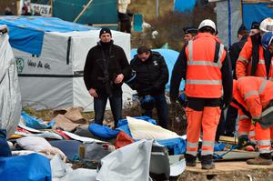"Policemen stand as  agents dismantle shelters on February 29, 2016 in the ""jungle"" migrants and refugees camp in Calais, northern France.  A French court on February 25 gave the green light to plans to evacuate hundreds of migrants from the southern half of the sprawling camp in the port town, with many wanting to stay near the entrance to the Channel Tunnel, the gateway to their ultimate goal of Britain. AFP PHOTO / PHILIPPE HUGUENPHILIPPE HUGUEN/AFP/Getty Images"