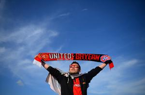 MANCHESTER, ENGLAND - APRIL 01:  A Manchester United fan holds up a matchday scarf ahead of the UEFA Champions League Quarter Final first leg match between Manchester United and FC Bayern Muenchen at Old Trafford on April 1, 2014 in Manchester, England.  (Photo by Michael Regan/Bongarts/Getty Images)