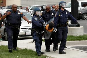 BALTIMORE, MD - APRIL 27:  Baltimore Police officers arrest a man near Mowdamin Mall, April 27, 2015 in Baltimore, Maryland. The funeral service for Freddie Gray, who died last week while in Baltimore Police custody, was held on Monday morning. (Drew Angerer/Getty Images)