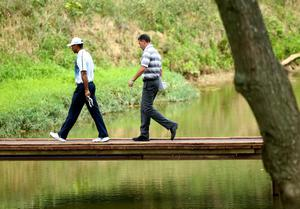 LOUISVILLE, KY - AUGUST 06: (L-R) Tiger Woods of the United States and sports agent Mark Steinberg walk across a bridge during a practice round prior to the start of the 96th PGA Championship at Valhalla Golf Club on August 6, 2014 in Louisville, Kentucky.  (Photo by Andy Lyons/Getty Images)