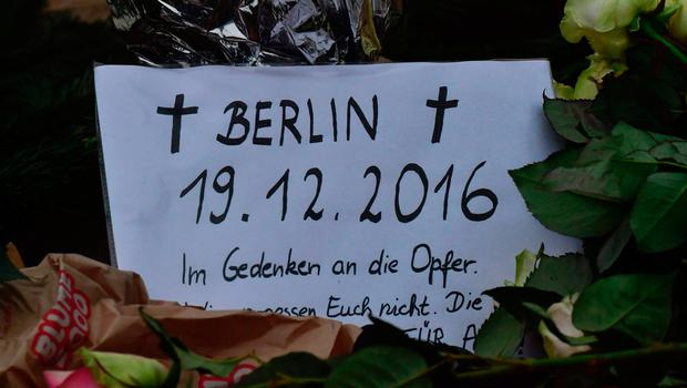 """A card reading in German 'In memory of the victims' is seen on December 20, 2016 at the site where a truck crashed into a Christmas market near the Kaiser-Wilhelm-Gedaechtniskirche (Kaiser Wilhelm Memorial Church) in Berlin. German police said they were treating as """"a probable terrorist attack"""" the killing of 12 people when the speeding lorry cut a bloody swath through the packed Berlin Christmas market. / AFP PHOTO / John MACDOUGALLJOHN MACDOUGALL/AFP/Getty Images"""