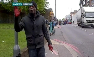 TV OUT.  INTERNET OUT. No cropping permitted. Picture must be credited to ITV. We are advised that videograbs should not be used more than 48 hours after the time of original transmission, without the consent of the copyright holder. Video grab taken from ITV News of a man holding weapons by the scene in John Wilson Street, Woolwich where a man was found murdered. PRESS ASSOCIATION Photo. Issue date: Wednesday May 22, 2013. A major police operation was launched today after two suspected terrorists murdered a man in the street in broad daylight. Eyewitnesses said the victim was hacked to death, with some suggesting his attackers tried to behead him, before charging at police when they arrived on the scene in Woolwich, south east London. See PA story POLICE Woolwich. Photo credit should read: ITV News/PA Wire NOTE TO EDITORS: This screengrab may only be used in for editorial reporting purposes for the contemporaneous illustration of events, things or the people in the image or facts mentioned in the caption. Reuse of the picture may require further permission from the copyright holder.