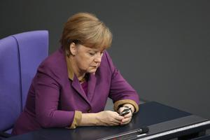 BERLIN, GERMANY - OCTOBER 25:  In this file photo German Chancellor Angela Merkel checks her mobile phone during a session of the Bundestag on November 30, 2012 in Berlin, Germany. German media reported on October 24, 2013 that German authorities had evidence that the National Security Agency has been eavesdropping on Merkel's mobile phone. Merkel telephoned the same day with U.S. President Barack Obama to complain and the incident has caused an international outcry among politicians across Europe.  (Photo by Sean Gallup/Getty Images)