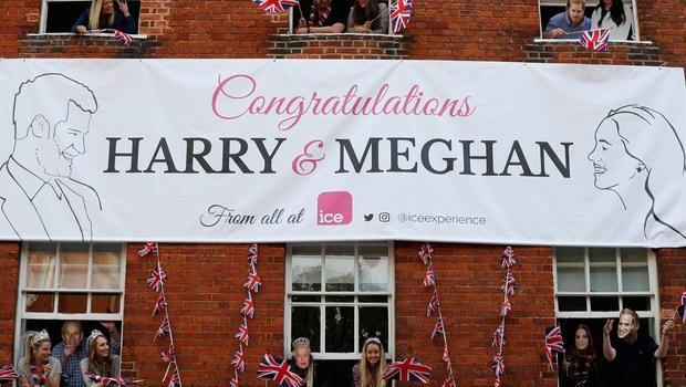 Royal fans lean out of windows as they watch Britain's Prince Harry and his best man Prince William, Duke of Cambridge, greet well-wishers on the street outside Windor Castle in Windsor on May 18, 2018, the eve of Prince Harry's royal wedding to US actress Meghan Markle.  Britain's Prince Harry and US actress Meghan Markle will marry on May 19 at St George's Chapel in Windsor Castle. / AFP PHOTO / Adrian DENNISADRIAN DENNIS/AFP/Getty Images
