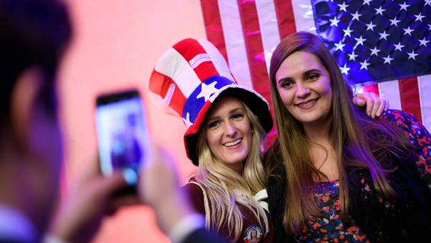 A supporter of Democrat candidate, wearing a hat with colours of the US national flag, poses for a picture during the US Election Night Celebrations in Switzerland in Geneva, on November 8, 2016. America's future hung in the balance on November 8, 2016 as millions of eager voters cast ballots to elect Democrat Hillary Clinton as their first woman president, or hand power to the billionaire populist Donald Trump. / AFP PHOTO / FABRICE COFFRINIFABRICE COFFRINI/AFP/Getty Images