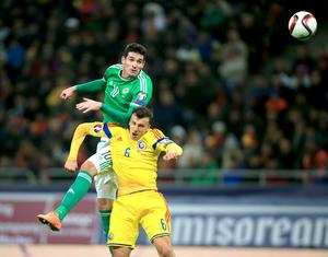 Northern Ireland's Kyle Lafferty (left) and Romania's Vlad Chiriches battle for the ball during the UEFA Euro 2016 qualifier at the Arena Nationala, Bucharest. Nick Potts/PA Wire.