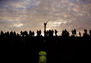 Migrants gather to attempt to overrun a police cordon by the perimeter fence of the Eurotunnel site at Coquelles in Calais, France. PRESS ASSOCIATION Photo. Picture date: Thursday July 30, 2015. Nine people have been killed attempting to cross the Channel in the last month, according to Eurotunnel, as migrants try to reach Britain. See PA story POLITICS Calais. Photo credit should read: Yui Mok/PA Wire