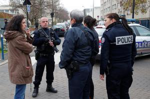 Police officers control the area near a pre-school after a masked assailant with a box-cutter and scissors who mentioned the Islamic State group attacked a teacher, Monday, Dec.14, 2015 in Paris suburb Aubervilliers. The assailant remains at large, and the motive for the attack is unclear, authorities said. (AP Photo/Michel Euler)