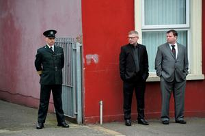 A police officer stands guard near mourners as the funeral of murdered prison officer Adrian Ismay takes place on March 22, 2016 in Belfast, Northern Ireland. Mr Ismay was seriously injured after a booby-trap device exploded under his van in east Belfast earlier this month. The 52 year old was thought to be recovering well from his injuries but died following a heart attack due to complications following the bomb attack. The new IRA, a dissident terrorist group have claimed responsibility for the murder.   (Photo by Charles McQuillan/Getty Images)