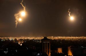 The sky and the city are lit by Israeli forces' flares in the northern Gaza Strip, Friday, July 18, 2014.(AP Photo/Lefteris Pitarakis)