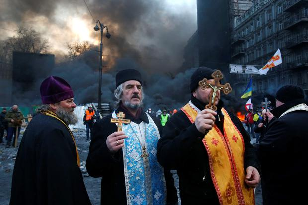 Priests of different faiths pray during clashes with police in central Kiev, Ukraine, Thursday, Jan. 23, 2014. Thick black smoke from burning tires engulfed parts of downtown Kiev as an ultimatum issued by the opposition to the president to call early elections or face street rage was set to expire with no sign of a compromise on Thursday. (AP Photo/Sergei Grits)