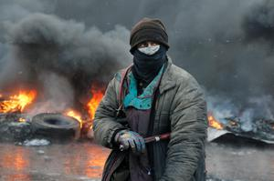 A protester stands at a burning barricades  between police and protesters in central Kiev, Ukraine, Thursday Jan. 23, 2014.  Thick black smoke from burning tires engulfed parts of downtown Kiev as an ultimatum issued by the opposition to the president to call early election or face street rage was set to expire with no sign of a compromise on Thursday. (AP Photo/Efrem Lukatsky)