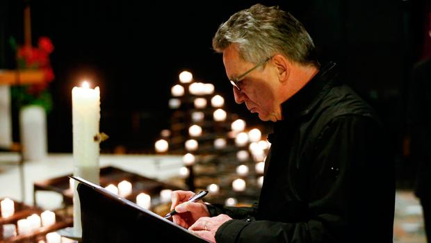 """German Interior Minister Thomas de Maiziere signs the book of condolences on December 20, 2016 inside the Kaiser-Wilhelm-Gedaechtniskirche (Kaiser Wilhelm Memorial Church), the day after an attack at the nearby Christmas market in central Berlin.  German police said they were treating as """"a probable terrorist attack"""" the killing of 12 people when the speeding lorry cut a bloody swath through the packed Berlin Christmas market. / AFP PHOTO / POOL / HANNIBAL HANSCHKEHANNIBAL HANSCHKE/AFP/Getty Images"""
