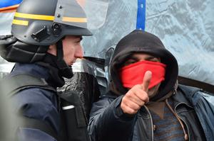 "A migrant gestures next to a policeman as agents dismantle shelters on February 29, 2016 in the ""jungle"" migrants and refugees camp in Calais, northern France.  A French court on February 25 gave the green light to plans to evacuate hundreds of migrants from the southern half of the sprawling camp in the port town, with many wanting to stay near the entrance to the Channel Tunnel, the gateway to their ultimate goal of Britain. AFP PHOTO / PHILIPPE HUGUENPHILIPPE HUGUEN/AFP/Getty Images"