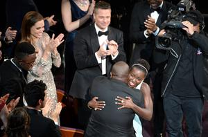 HOLLYWOOD, CA - MARCH 02:  Actress Lupita Nyong'o (R), winner of the Best Performance by an Actress in a Supporting Role award for '12 Years a Slave,' with director Steve McQueen (C) as actress Angelina Jolie (top L) and actor/producer Brad Pitt (top C) look on during the Oscars at the Dolby Theatre on March 2, 2014 in Hollywood, California.  (Photo by Kevin Winter/Getty Images)