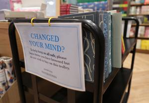 A trolley for books that have been browsed but not purchased by customers in a London branch of Waterstones (Yui Mok/PA)