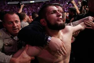 Khabib Nurmagomedov is held back outside of the cage after fighting Conor McGregor in a lightweight title mixed martial arts bout at UFC 229 in Las Vegas, Saturday, Oct. 6, 2018. Nurmagomedov won the fight by submission during the fourth round to retain the title. (AP Photo/John Locher)
