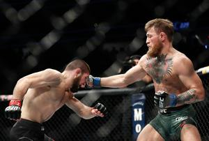 Conor McGregor, right, punches Khabib Nurmagomedov during a lightweight title mixed martial arts bout at UFC 229 in Las Vegas, Saturday, Oct. 6, 2018. (AP Photo/John Locher)